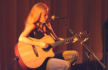 Candice Jarrett playing guitar and harmonica